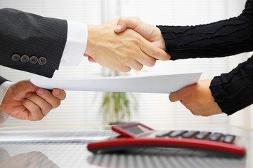 businesswoman-and-businessman-are-handshaking-and-exchanging-con