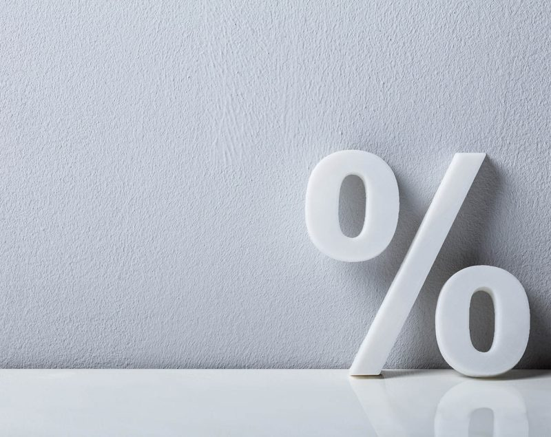 close-up-of-a-percentage-sign-leaning-on-white-wall
