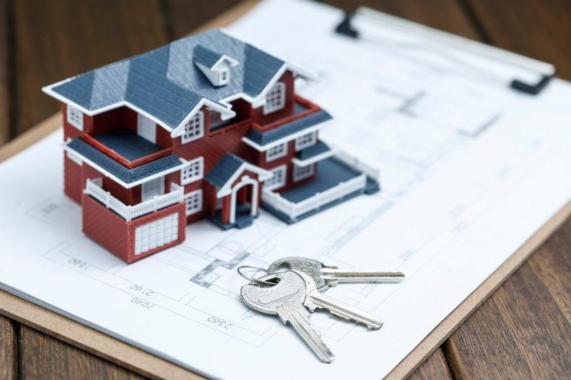 villa-house-model-key-and-drawing-on-retro-desktop-real-estate-sale-concept